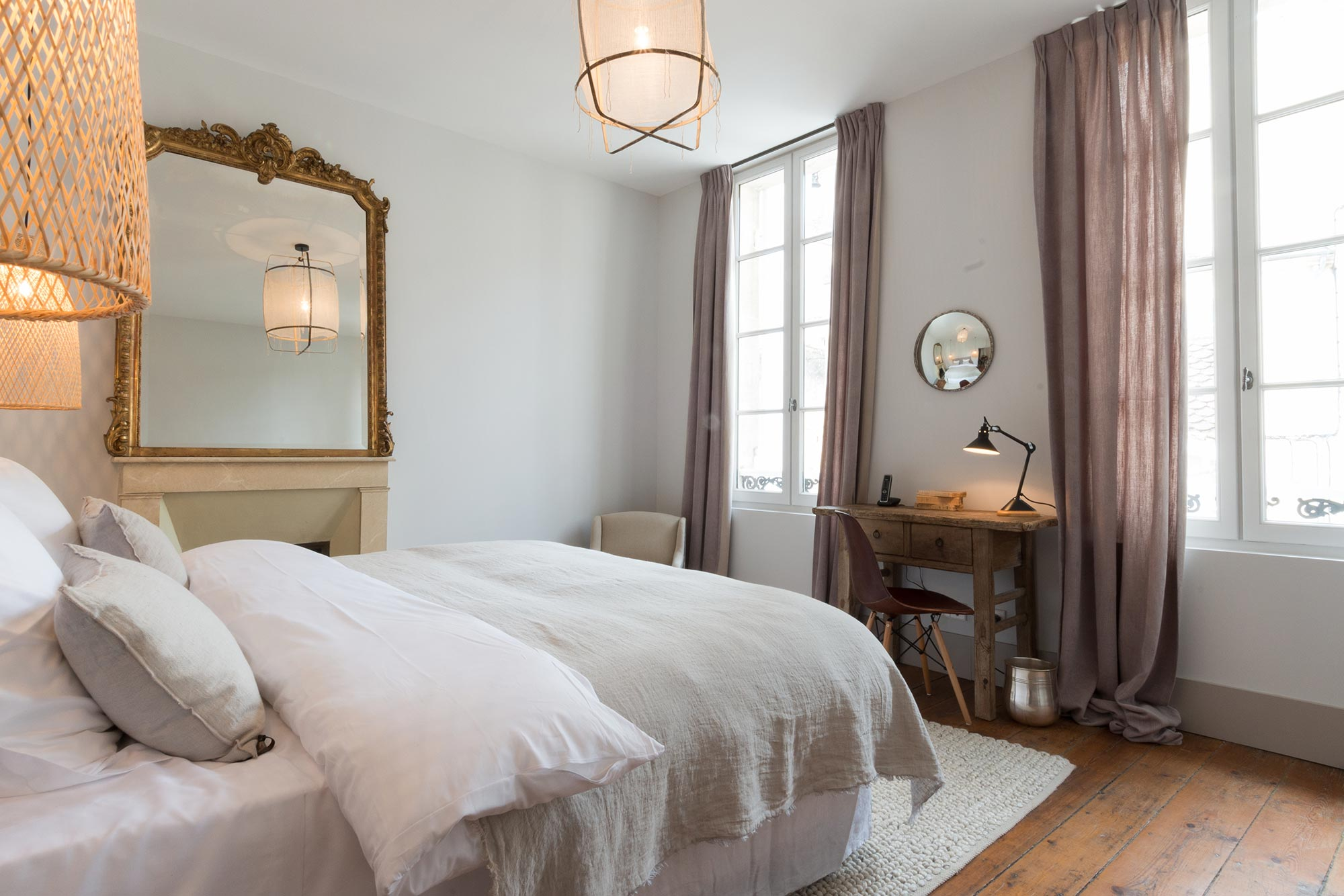 Chambre lit double, détail suspension en rotin illuminée, lumière tamisée, quelques miroirs en décoration et linge de lit couleur lin et ivoire