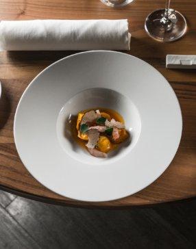 plat dans une assiette creuse blanche posée sur une table dressée