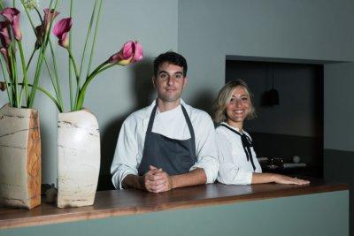 Femme blonde et homme brun l'un à côté de l'autre, en tabliers vert, derrière un comptoir d'accueil