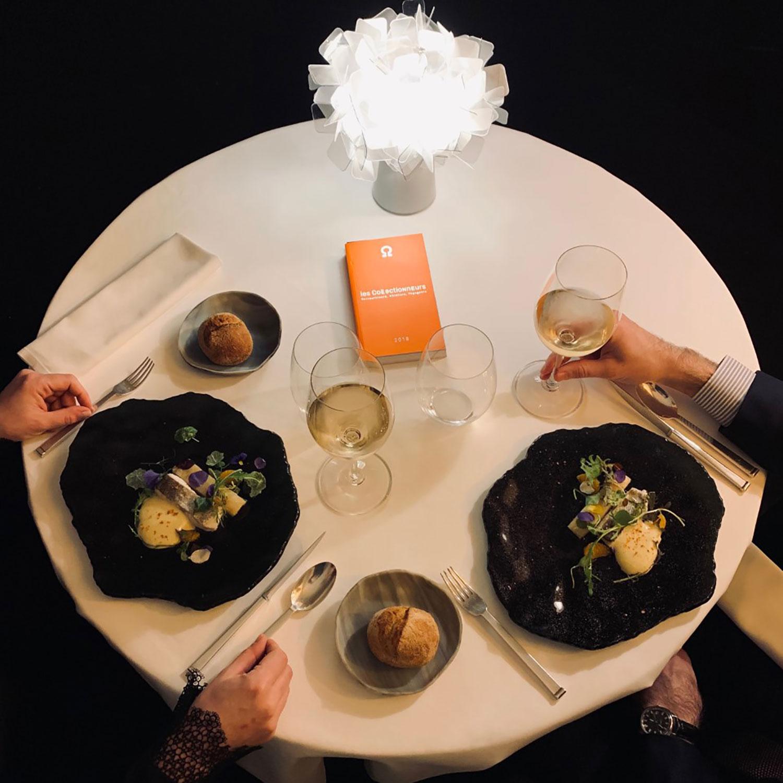 Table dressée pour deux personnes avec assiette noir présentation plat de poisson, assiette à pain, à droite un bras d'homme et à gauche un bras de femme