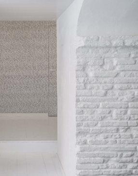 Mur blanc en brique entrée de couloir avec mur en fond avec inscriptions lettres capitales noires