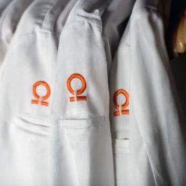 Détail sur épaule de veste de cuisinier brodée d'un oméga orange