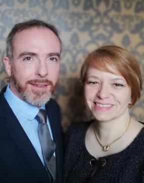 Photo d'un couple, homme en costume et chemise bleu à gauche, femme en t-shirt col rond noir et cheveux court