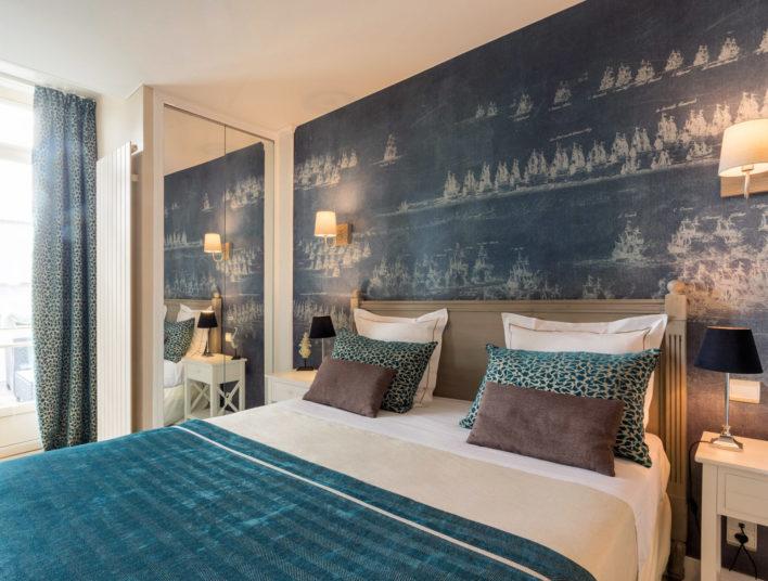 Chambre décoration bleu avec lit double, linge de lit bleu et blanc