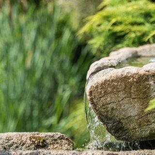 Détail fontaine avec de l'eau qui coule sur une pierre