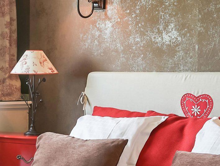 Détail décoration tête de lit couleur lin, coussin rouge, marron et blanc, deux lampes de chevets dont une applique