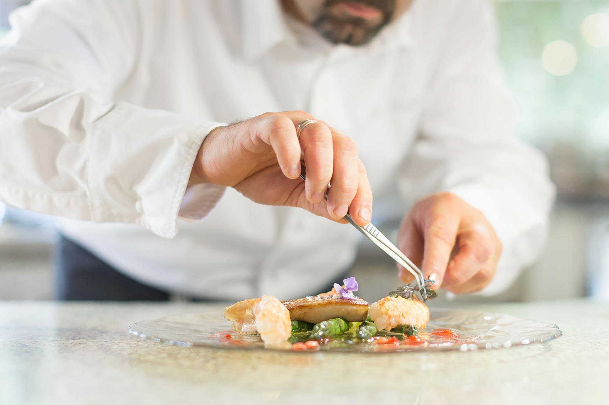 détail sur mains d'un chef dressant une assiette avec une petite pince de précision