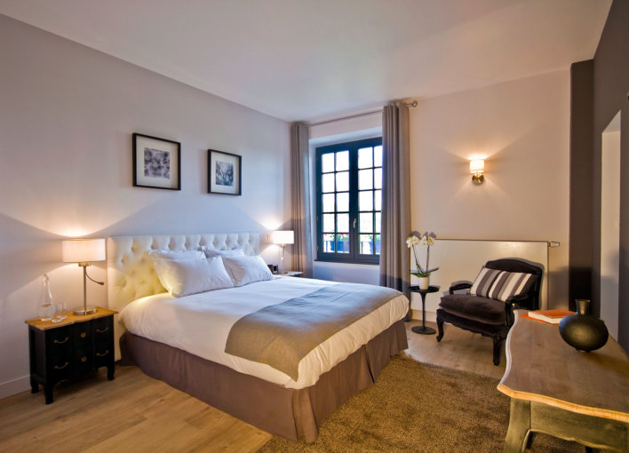 Chambre lit double, tête de lit capitonnée et tapis doré bronze