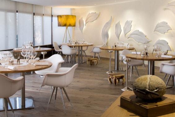 Salle de restaurant avec chaise style scandinave, tables rondes et mur décoré de grandes feuilles blanche