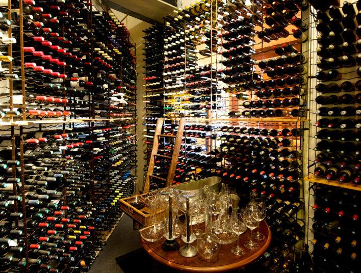 Cave avec plusieurs bouteilles de vin et table de dégustation