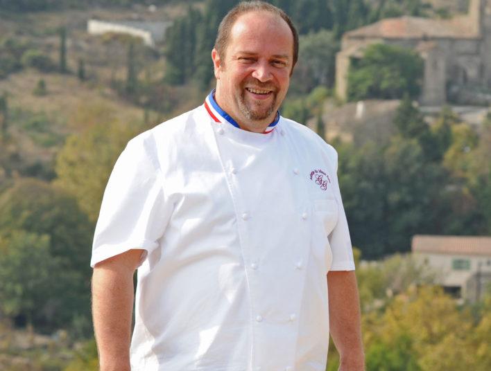 Chef en tenue de cuisinier avec le col des MOF Meilleurs Ouvriers de France
