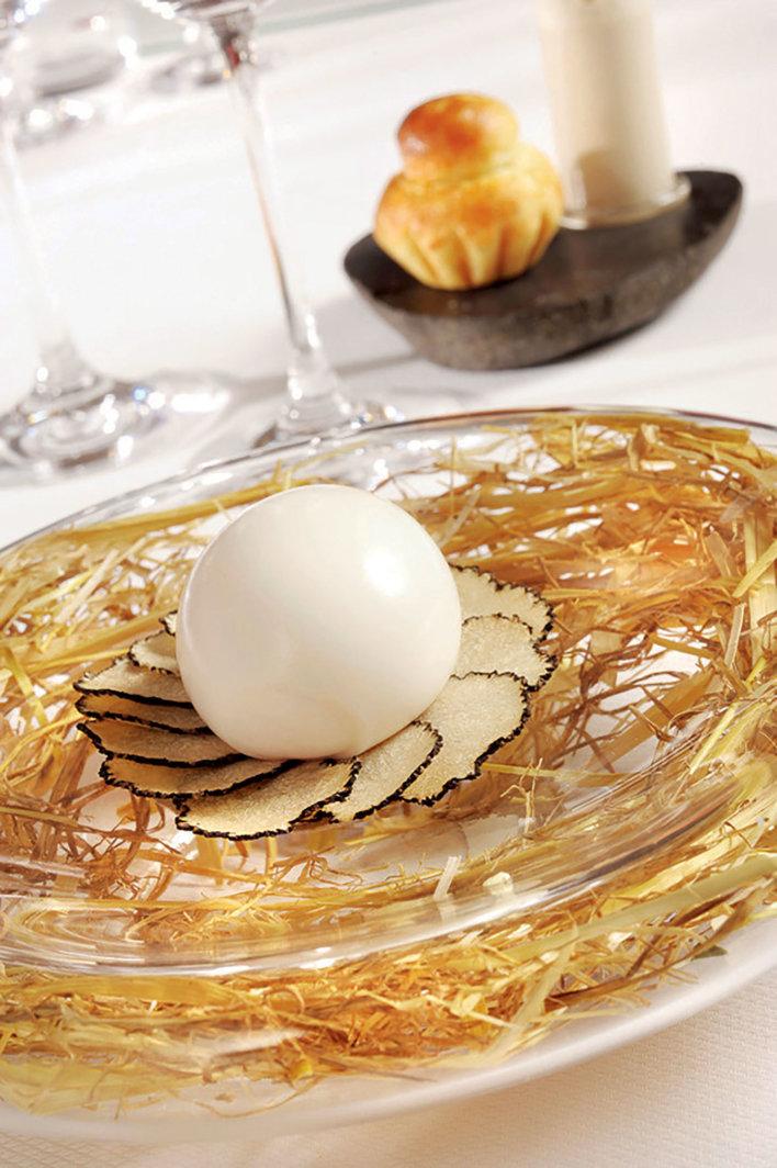 Un œuf posé sur des pétale de truffes dans une assiette transparente contenant du foin