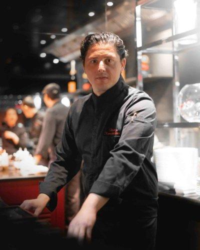 Portrait d'un chef devant un bar de restaurant, en veste noir