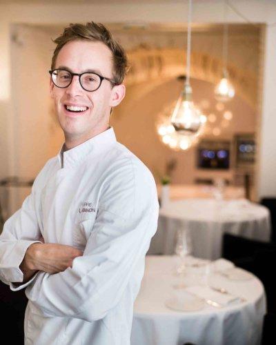 Portrait chef en veste blanche et dans sa salle de restaurant