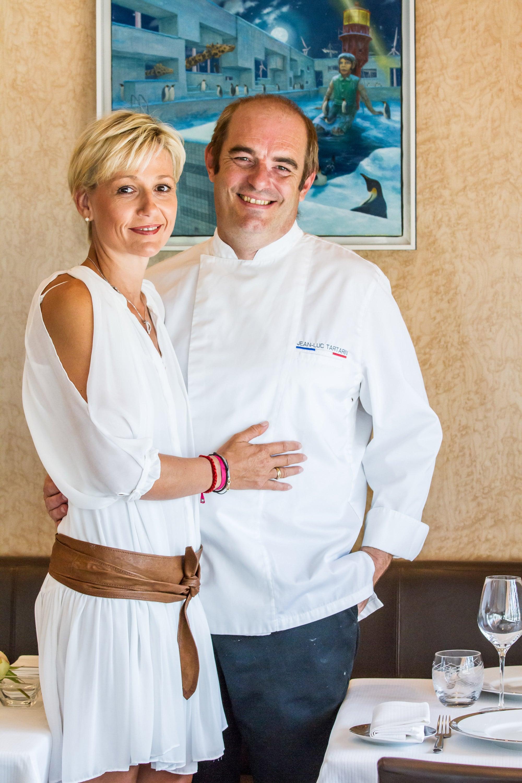 Annabelle habillé en blanc avec une ceinture marron qui est a coter de son mari avec sa main poser sur lui, et Jean-Luc Tartarin habillé de son tablier blanc et d'un pantalon qui à posé sa main derrière le dos de sa femme