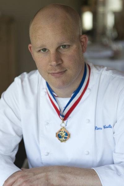 Photo portrait d'un chef en veste de cuisinier blanche, décoré du col bleu blanc rouge de Meilleur ouvrier de France, veste brodée bleue au nom du chef, soit Pierre Caillet