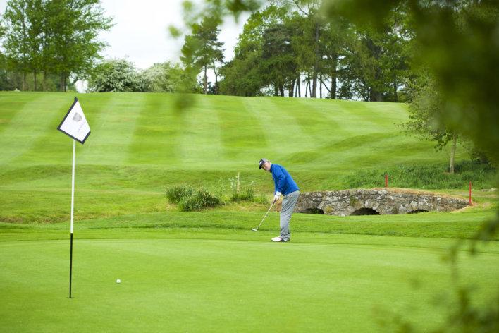 Golfeur en polo bleu, vue de profil, tenant son club de golf dans les deux mains prêt à tirer dans une balle