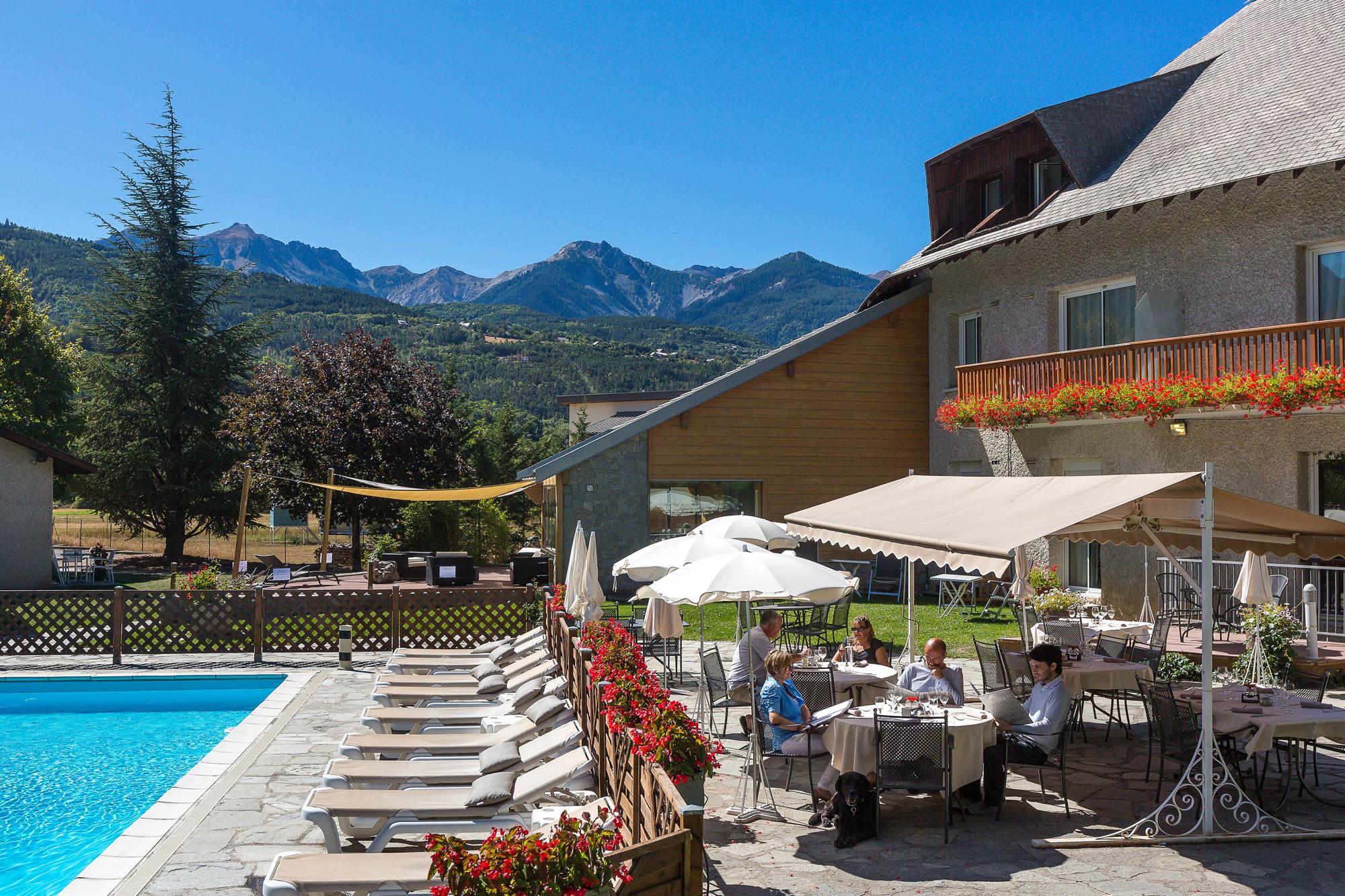 Photo de l'extérieur de l'établissement avec vue sa piscine et restaurant extérieur mais surtout sur les montagnes