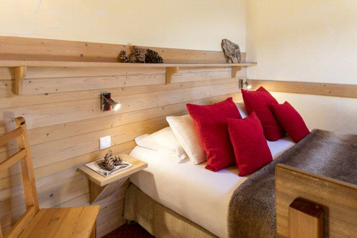 photo du haut du lit double avec ses beaux oreillers rouge