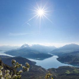 Plan panoramique sur des montagnes, une rivière, un grand ciel bleu et le soleil au centre de la photo