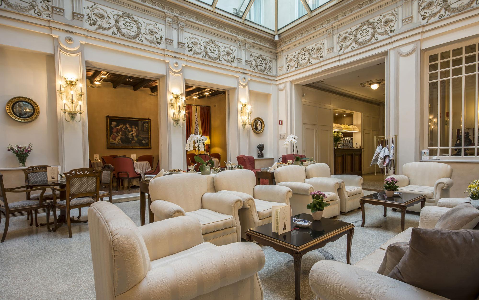 Grand salon, canapé couleur ivoire, grande verrière et décoration murale faite d'ornements