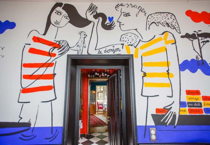 Entrée de restaurant décorée de dessins notamment deux personnages dessinés et peint de rouge, bleu et jaune par le créateur de mode Jean-Charles de Castelbajac
