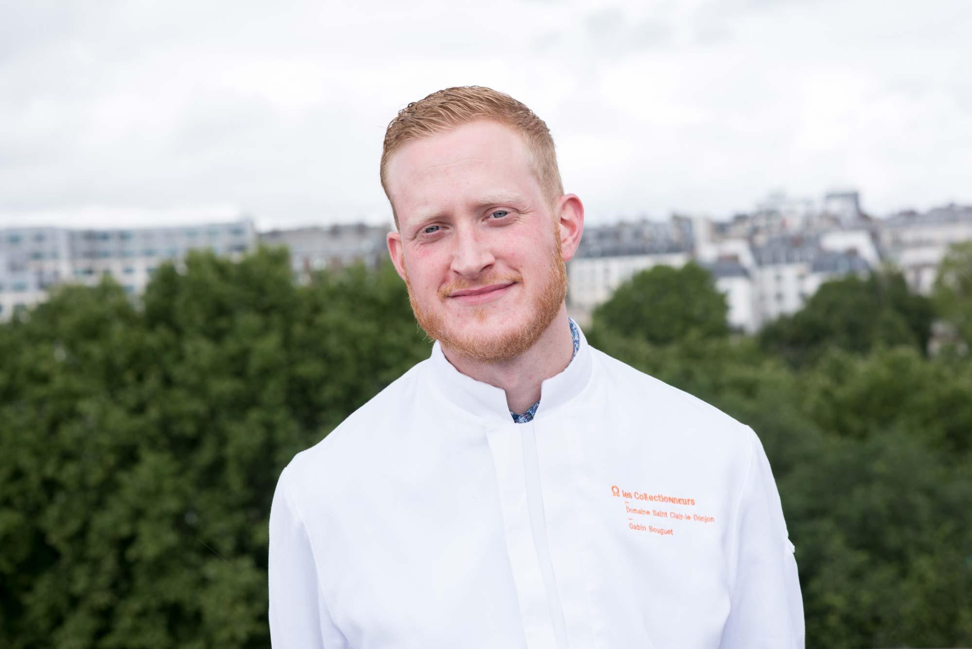 Photo portrait d'un chef en veste de cuisine blanche logotée les Collectionneurs et brodée au nom du chef, soit Gabin Bouguet