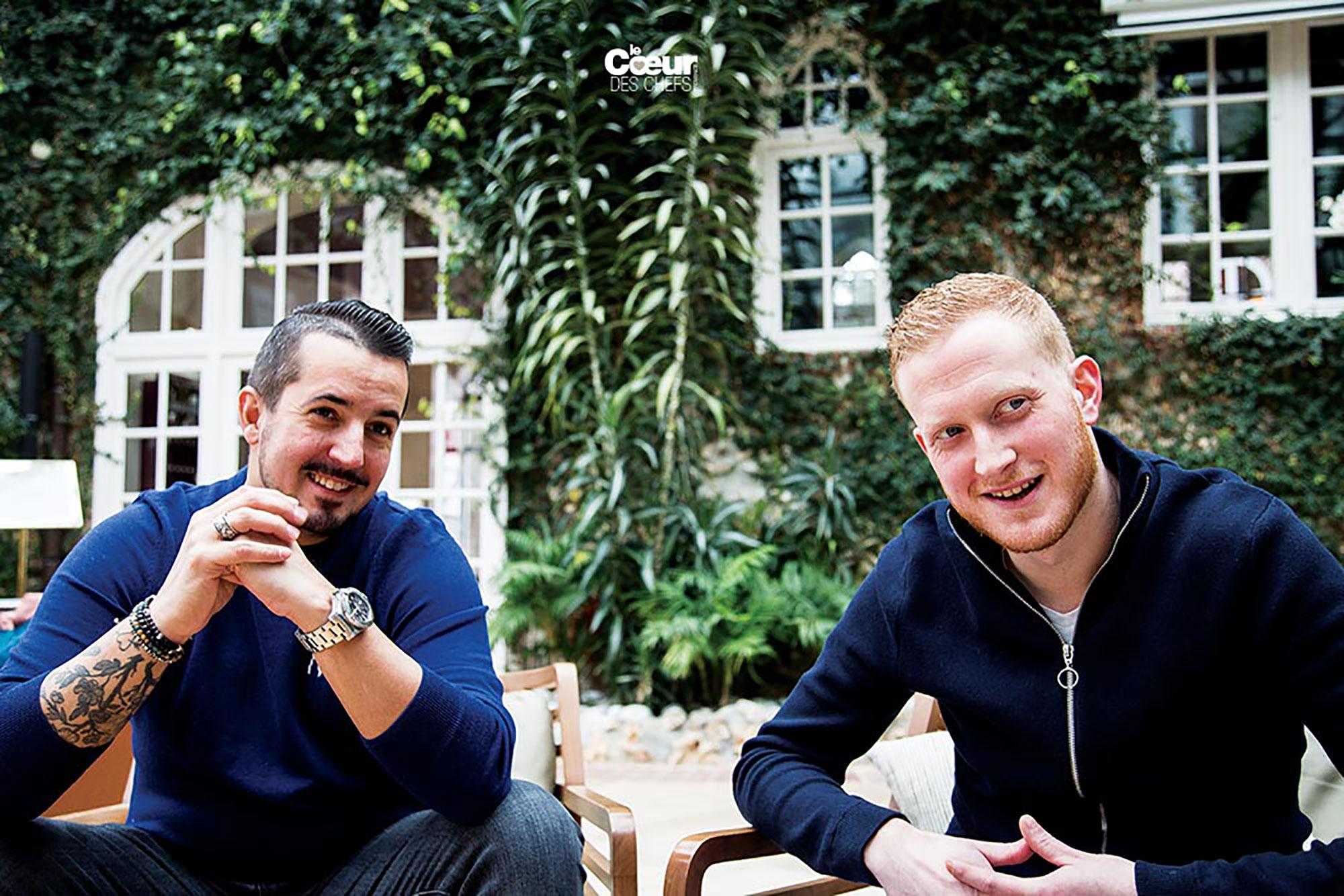 Photo de deux hommes assis en terrasse en pull et veste bleu, arrière plan mur de maison recouvert de lier
