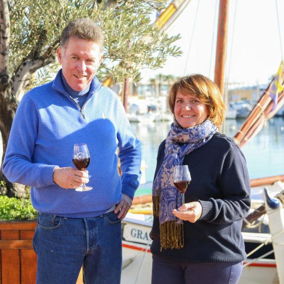 Photo d'un couple, un homme à gauche en pull bleu et une femme à droite en chandail bleu marine et écharpe nouée au cou, les deux tiennes un verre de vin rouge à la main