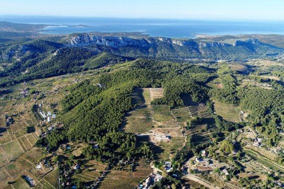 Vue aérienne panoramique sur les monts à la végétation typique de la provence, en arrière plan à l'horizon la mer