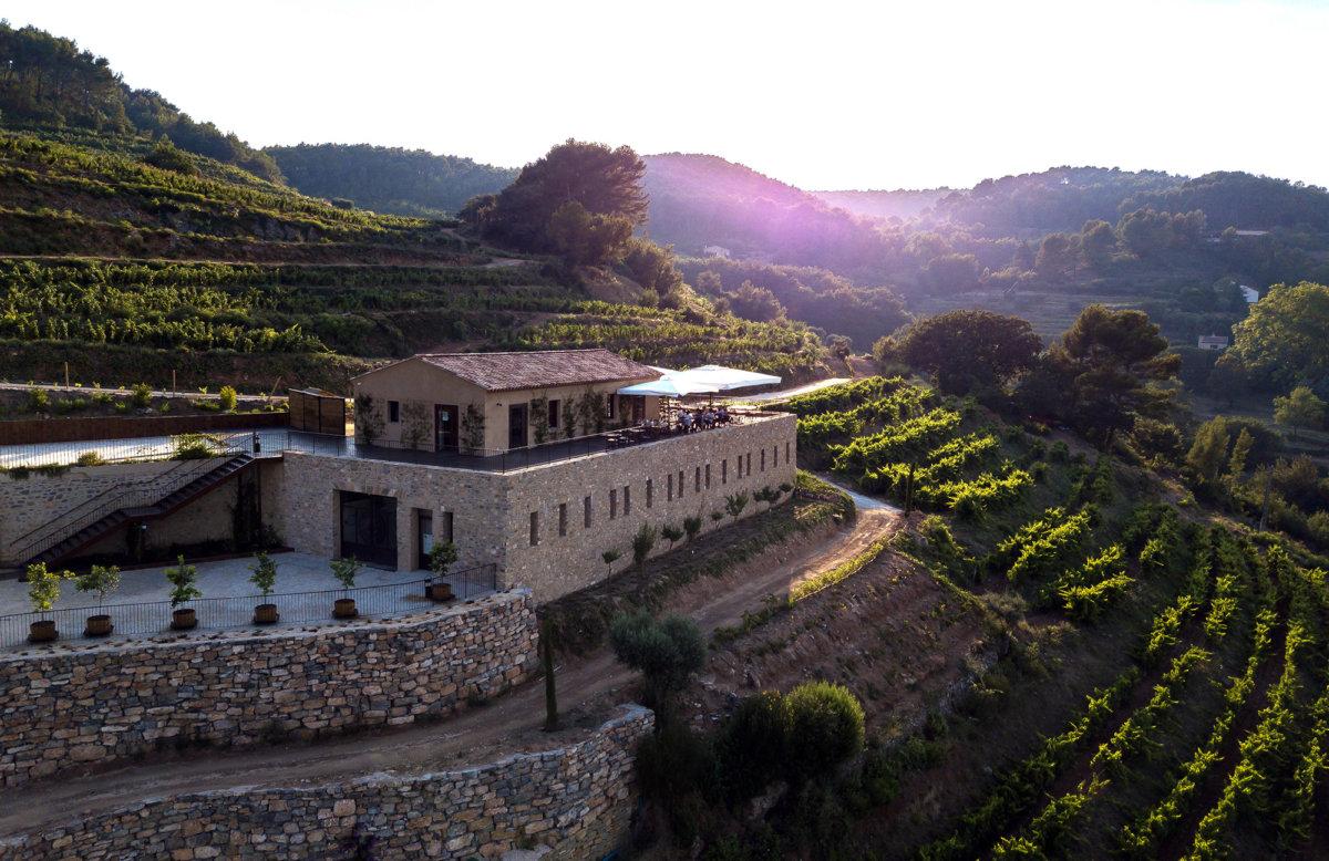 Photo prise avec un drone sur une bâtisse typique provençale, coucher de soleil en arrière plan et plan de vigne sur une coline