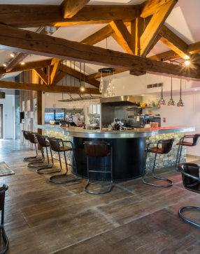Salle de restaurant avec cuisine ouverte, poutre apparentes et mobilier dans un mélange bois et acier