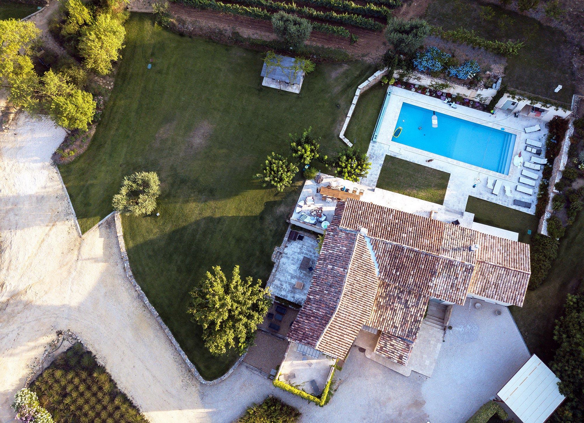 Vue aérienne d'une villa provençale en tuiles oranges et piscine extérieure