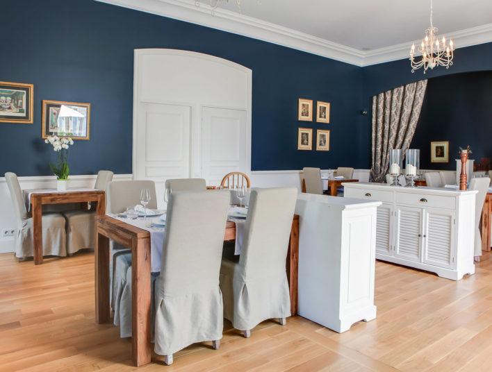 Salle à mangé, mur bleu, housse de chaises beige, table en bois et desserte en bois blanc