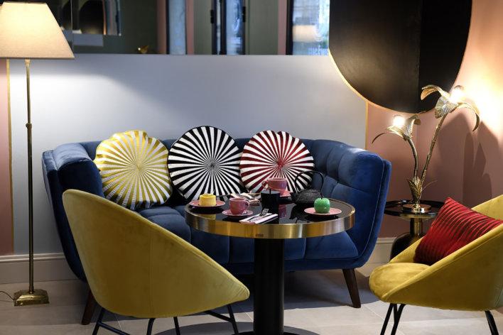 salon canapé bleu marine, fauteuil jaune et coussin rond bicolore ambiance art déco