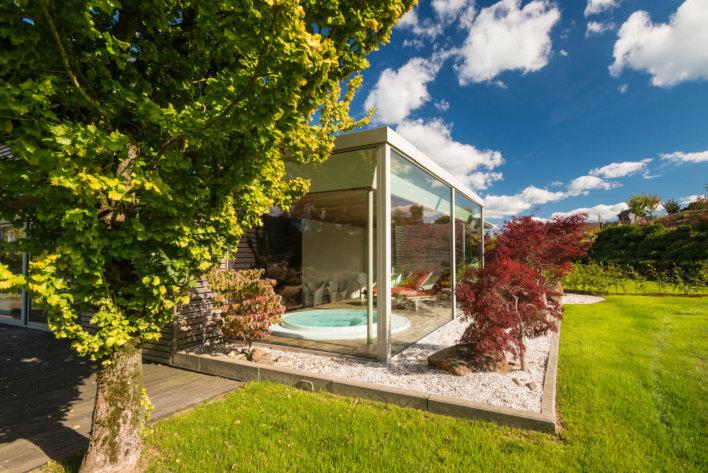 Jacuzzi extérieur vitré avec un,e belle vue sur l'espace vert de l'établissement