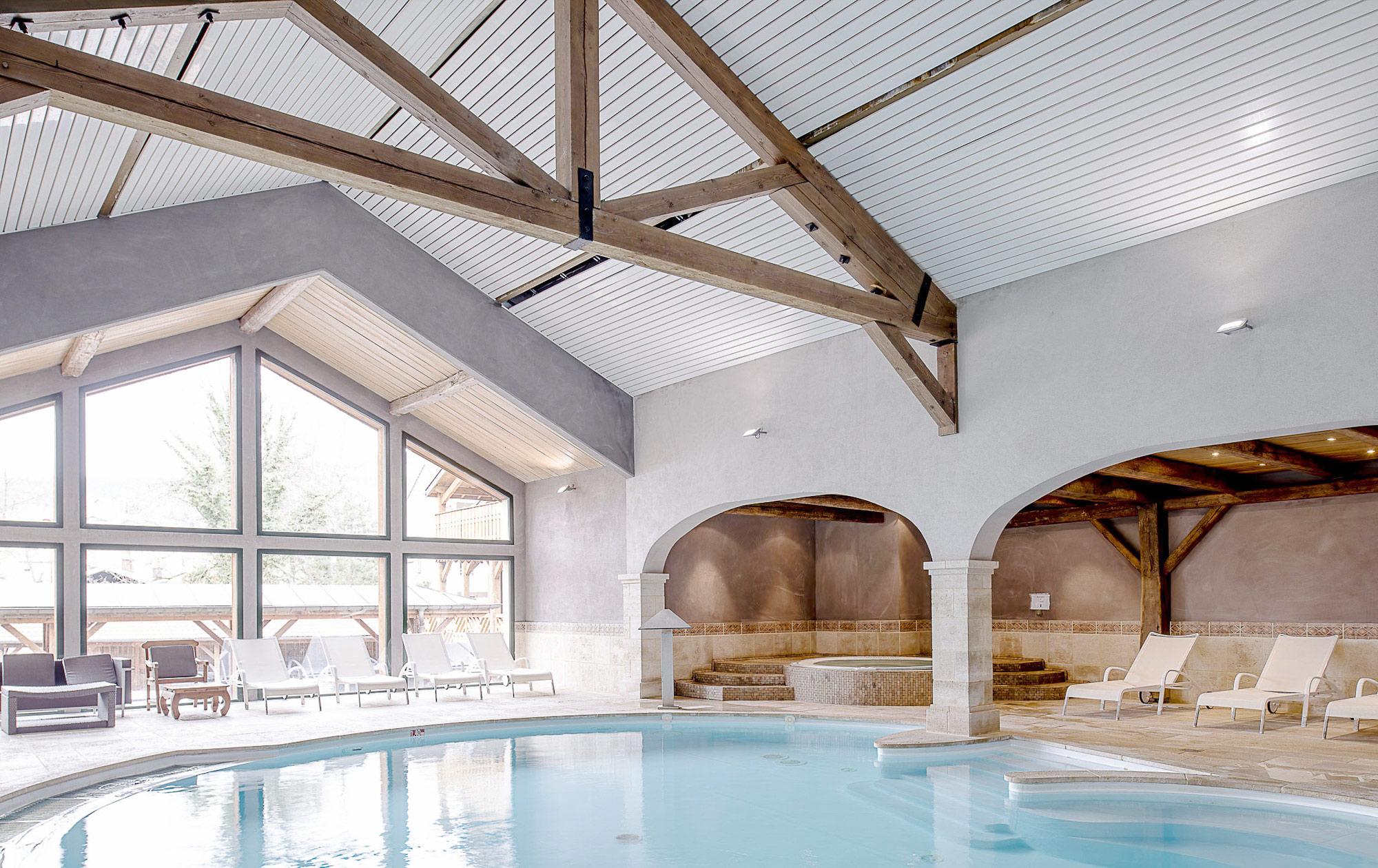 Espace détente avec une grande piscine intérieur
