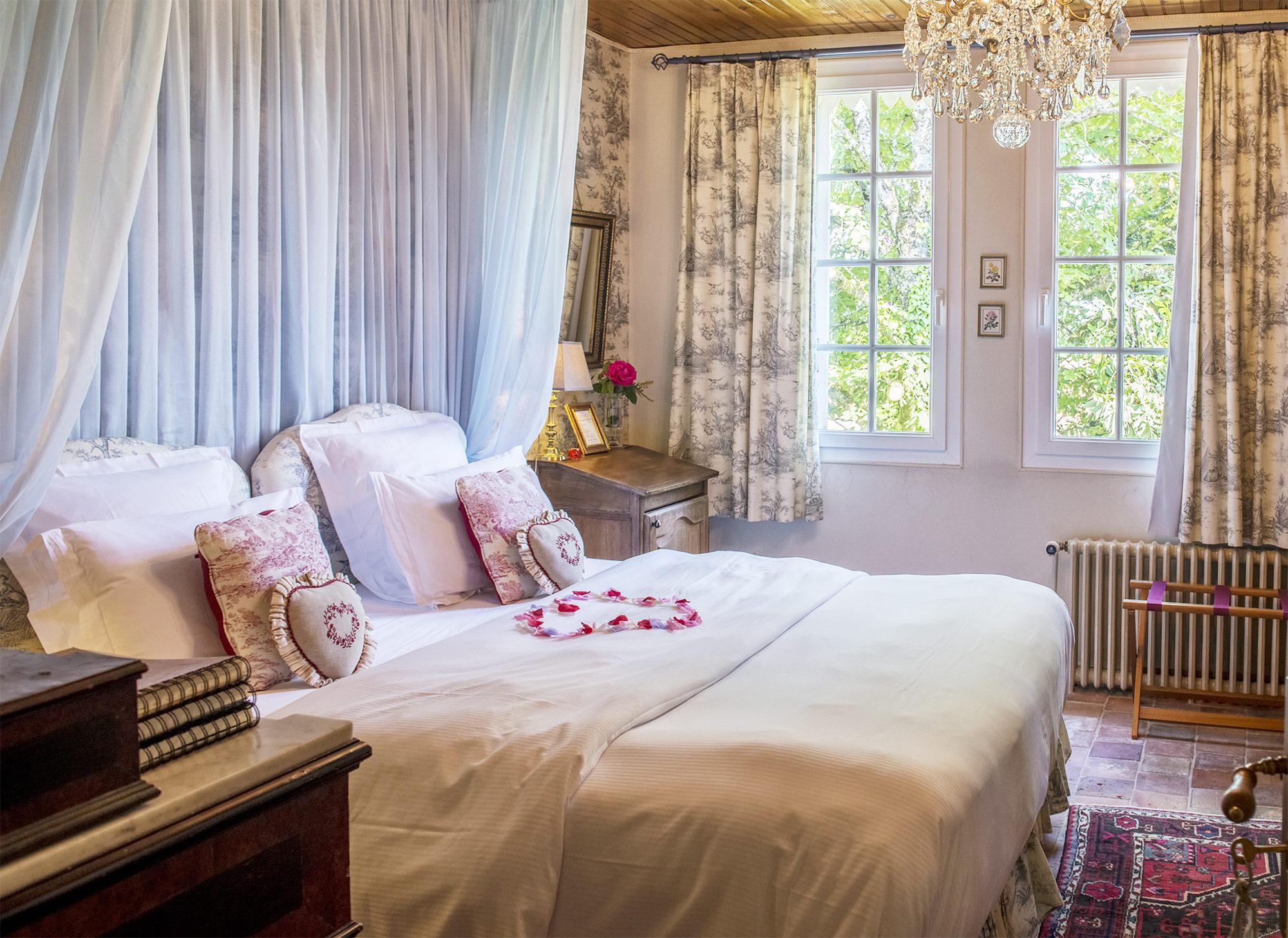Suite romantique avec des pétales de rose en forme de coeur sur le lit