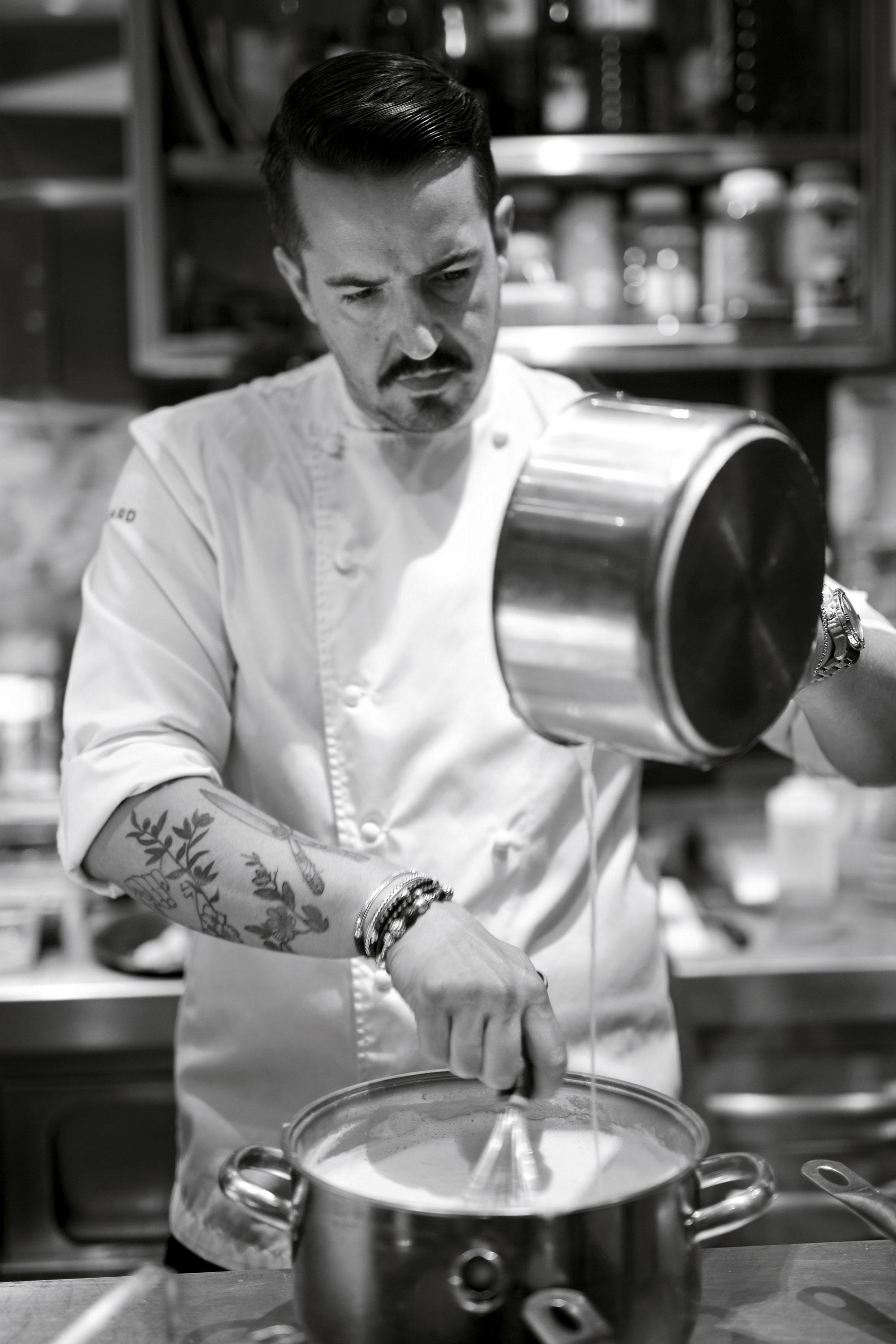 Le chef Olivier Da Silva en train de verser un mélange dans une casserole, la photo est en noir et blanc