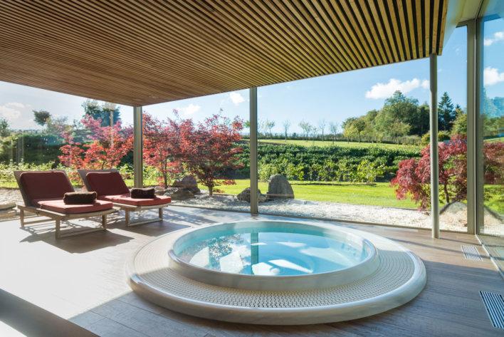 Jacuzzi intérieur pris en photo de l'intérieur avec une magnifique vue, qui donne sur l'espace vert de l'établissement