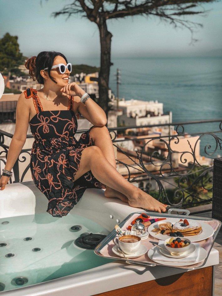 Femme assise sur le bord d'un jacuzzi avec petit-déjeuner sur un plateau