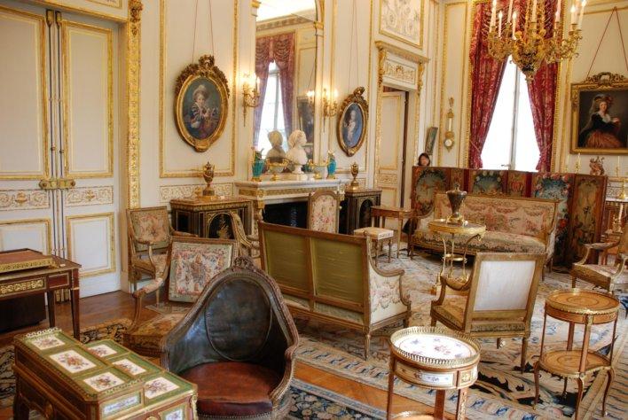 Pièce d'appartement typiquement parisien, meuble ancien, long rideaux, haut plafond et cheminée avec trumeau