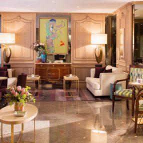 Photo d'un salon avec fauteuil, canapés, miroir et peinture, vase avec fleurs