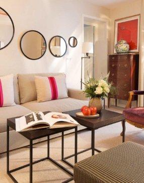 Salon d'une suite avec canapé, luminaire mural, fauteuil Louis XV et porte fenêtre