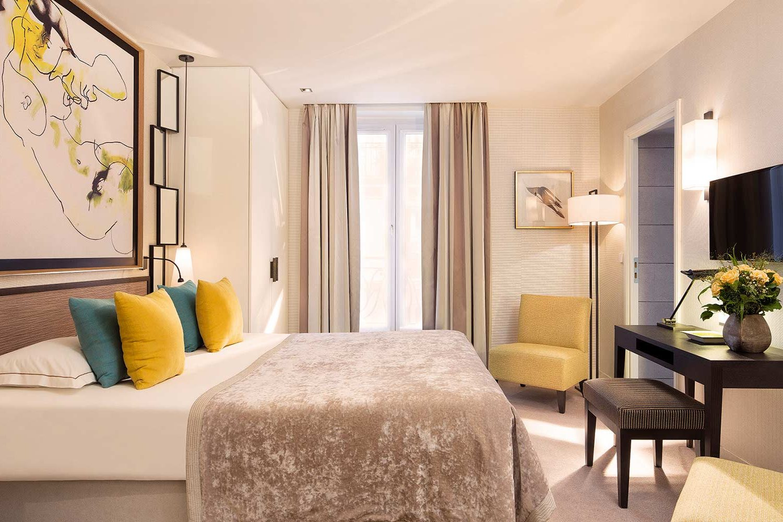 Chambre avec lit double, tête de lit toile peinte, fauteuil jaune et coussins jaune et bleu, détail déco miroir