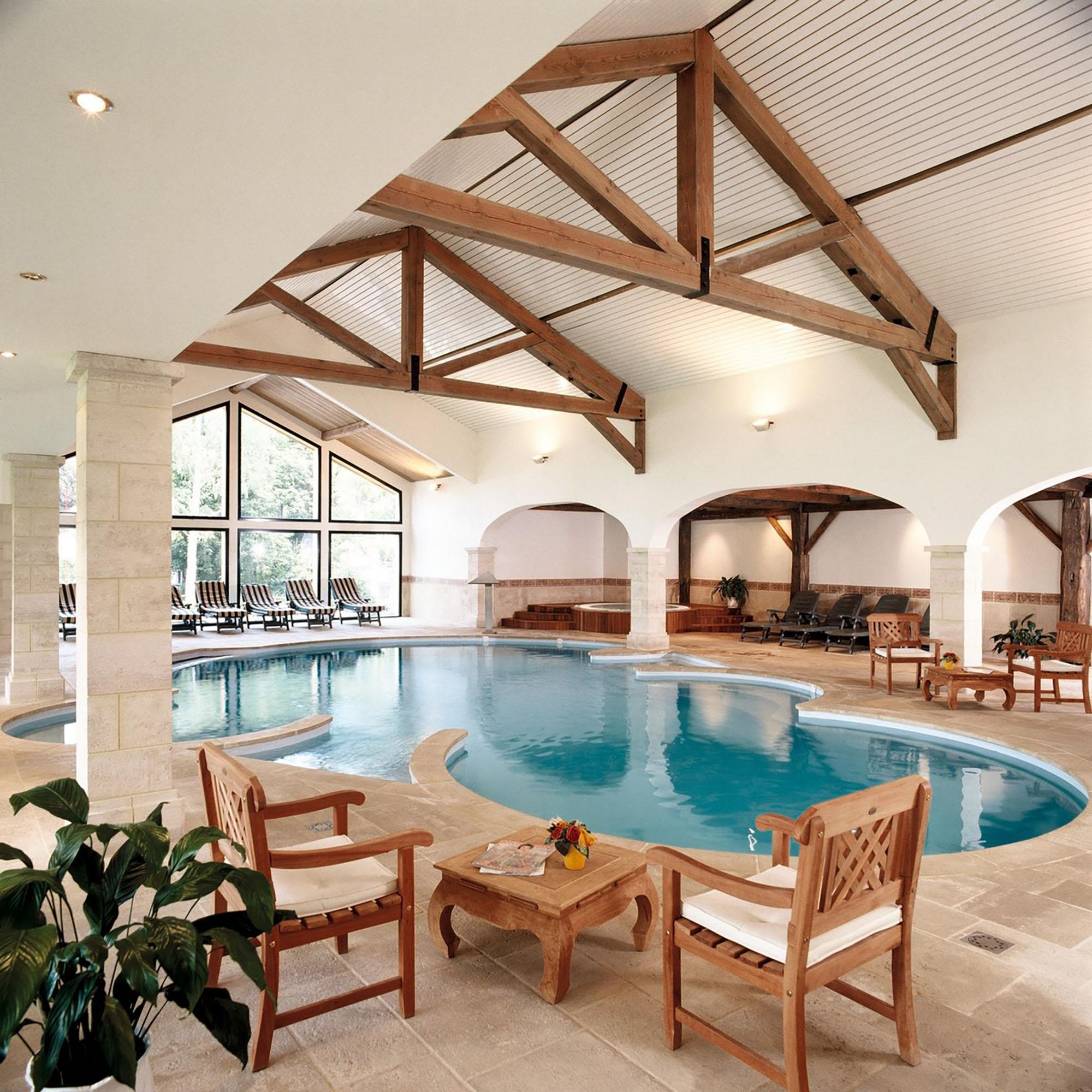 Espace détente avec deux chaise et une petite table d'un coter de la piscine et deux autres chaise avec une petite de l'autre coter de la piscine