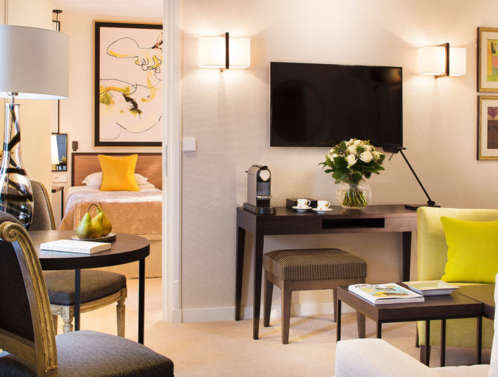 Salon d'une suite d'hôtel, ouvert sur une chambre, on aperçoit la tête de lit, des tables basses sont décorées de fruits et de livres, décoration et linge de lit dans les tons jaunes