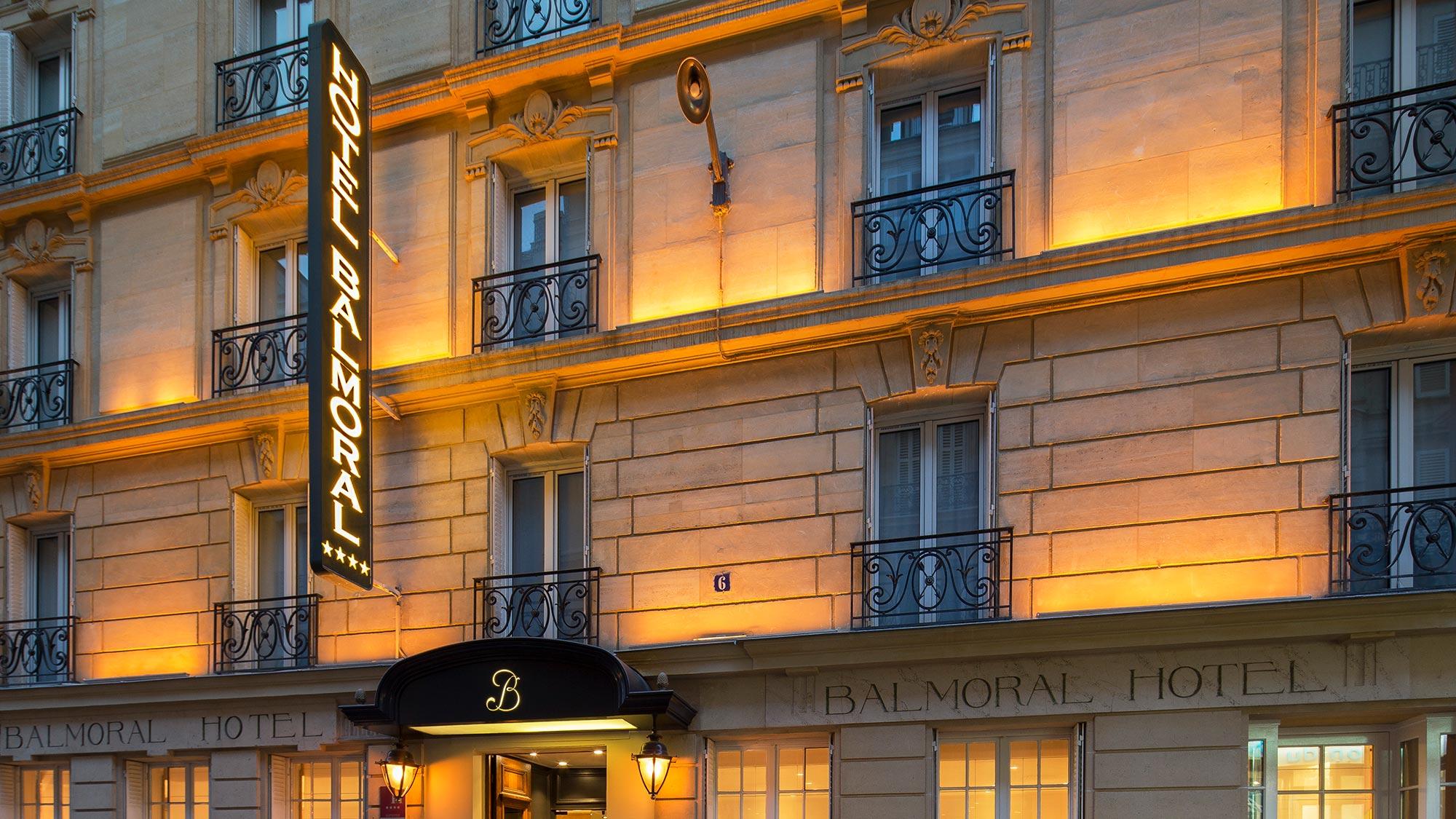 Façade d'un hôtel parisien en pierres de Paris, plusieurs fenêtre donnent sur rue, une enseigne contient l'inscription Hôtel Balmoral