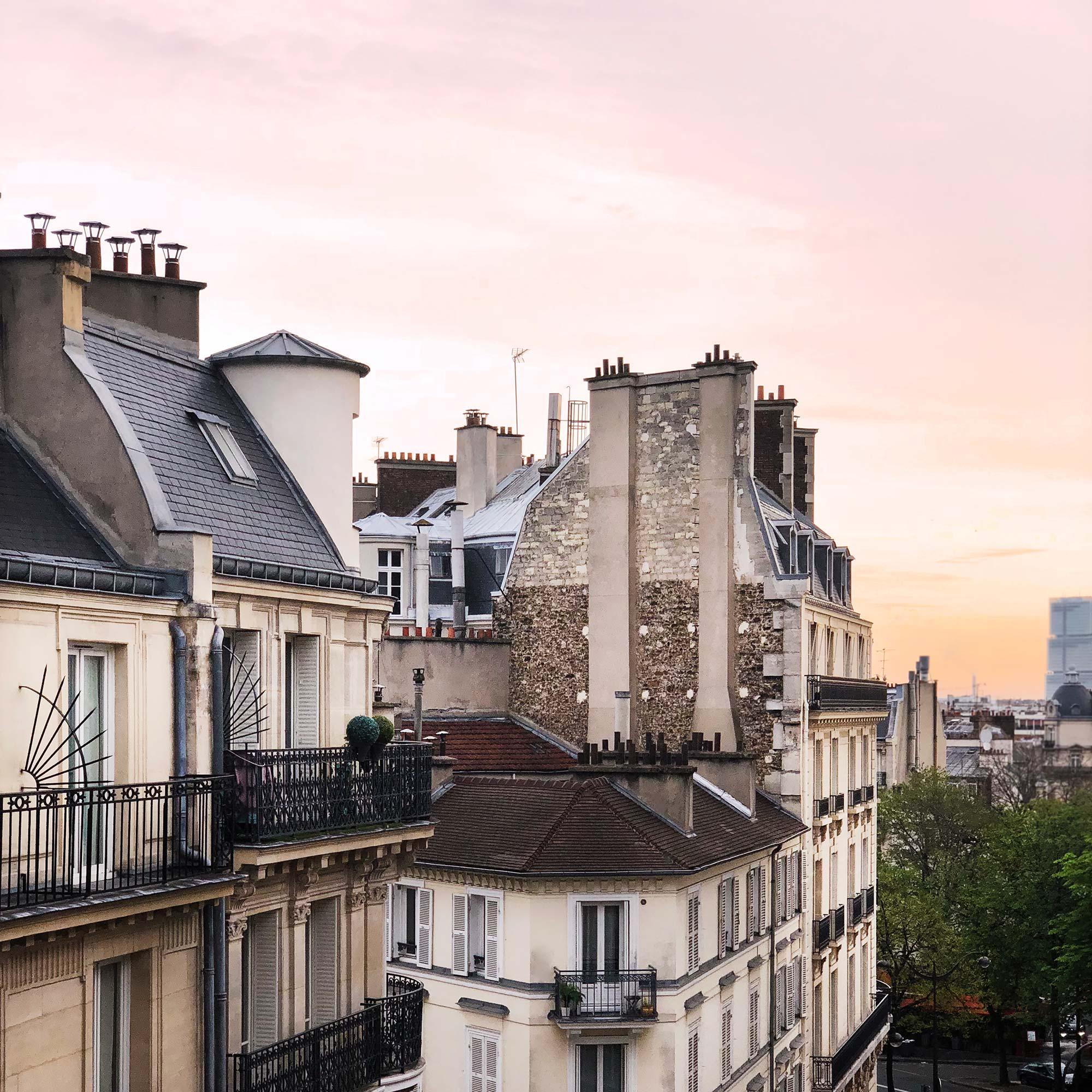 Vue sur les toits de Paris, un coucher de soleil en arrière plan