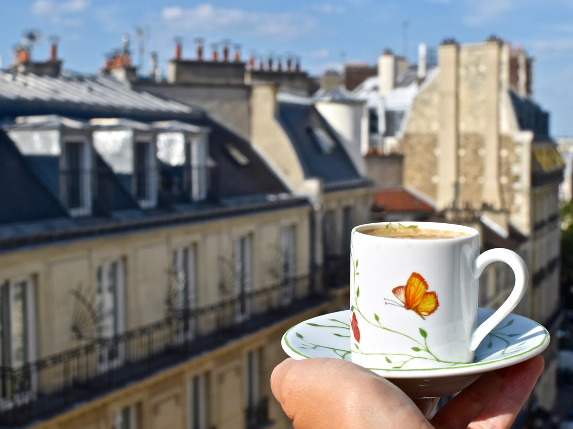 Close-up sur un café et la vue sur les toits de Paris floutée en arrière-plan
